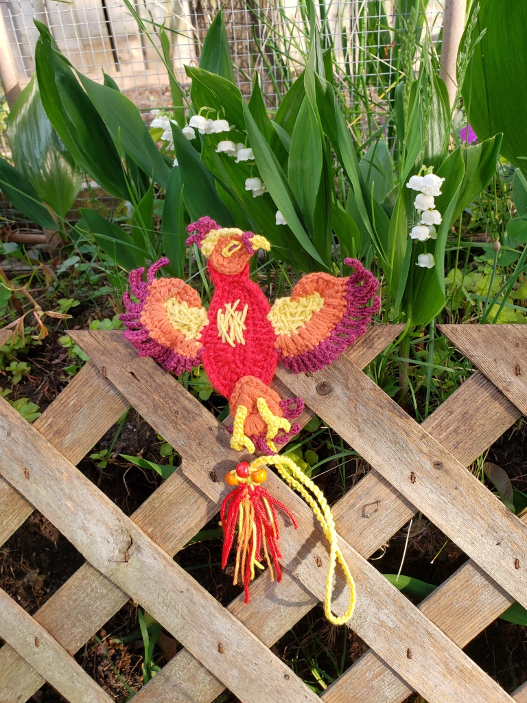 Image of a crochet phoenix bookmark with a backdrop of lily of the valley flowers in a garden box