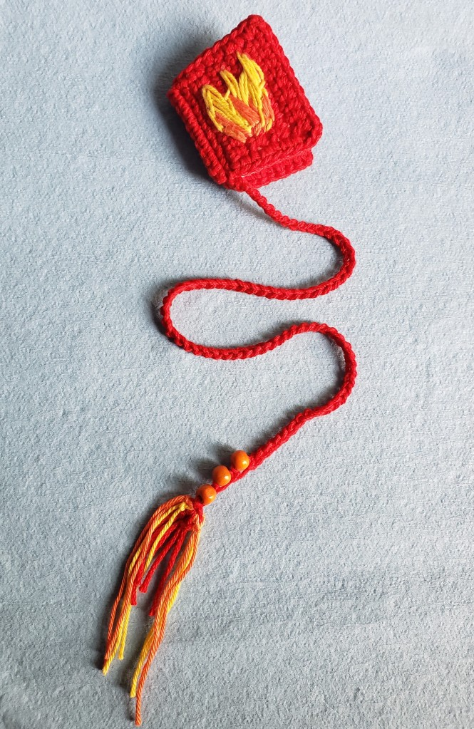 Crochet bookmark of red books with flames on the front, inspired by the The Library Book by Susan Orlean, and made by Peachy Books.