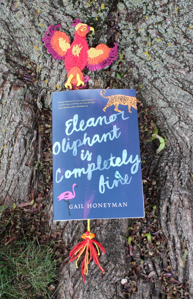 Image of Eleanor Oliphant is Completely Fine book with a crochet red, orange, yellow, and plum phoenix from the flames bookmark