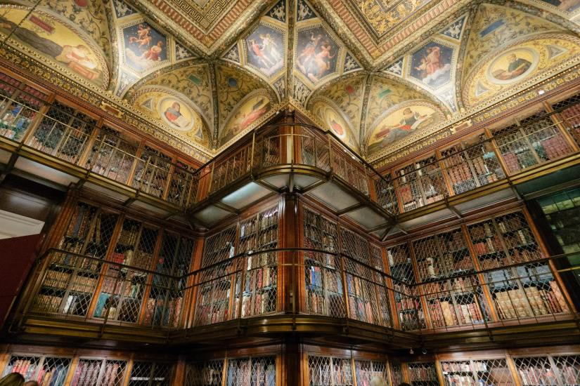 Image of a grand library with a ceiling painted with various depictions of books