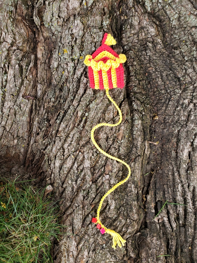 Crochet Bookmark of a red and yellow striped circus tent with a yellow flag on top