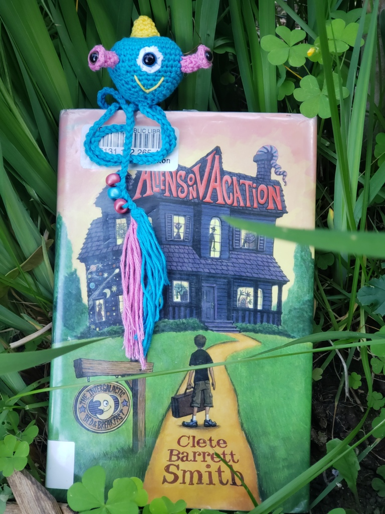 Image of Aliens on Vacation by Clete Barrett Smith with a blue alien crochet bookmark