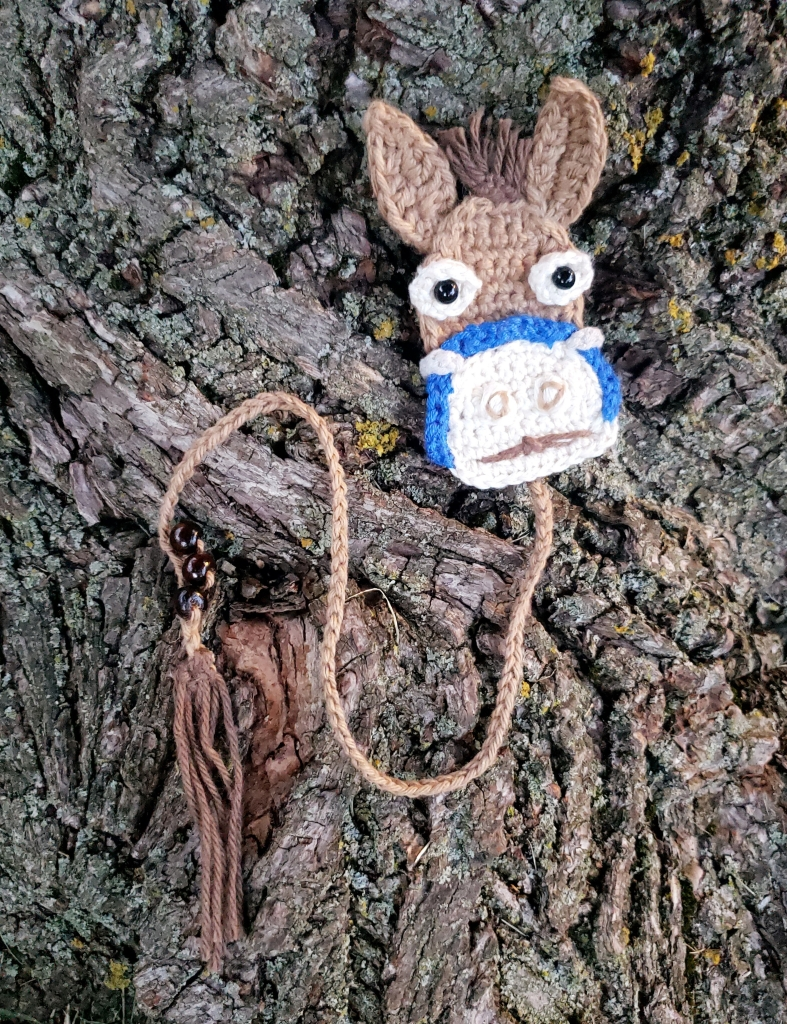 Crochet bookmark of a tan coloured mule with a blue bridle and brown tail