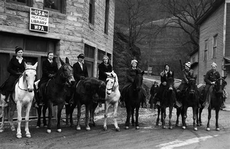 Picture showing librarians mounted on horse back posing for the photograph, underneath a sign that says: USA Pack Horse Library WPA on the building they are standing in front of.