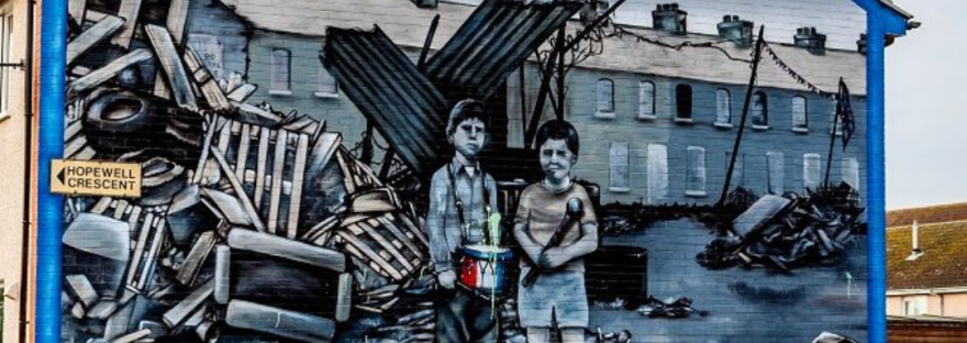 Image of a mural in Northern Ireland showing 2 boys standing in front of a war torn complex with heaps of debris, with a red title on top reading: Summer of 69, which says: Don't miss Murals of Northern Ireland, a companion post to my recent review of Say Nothing by Patrick Radden Keefe.
