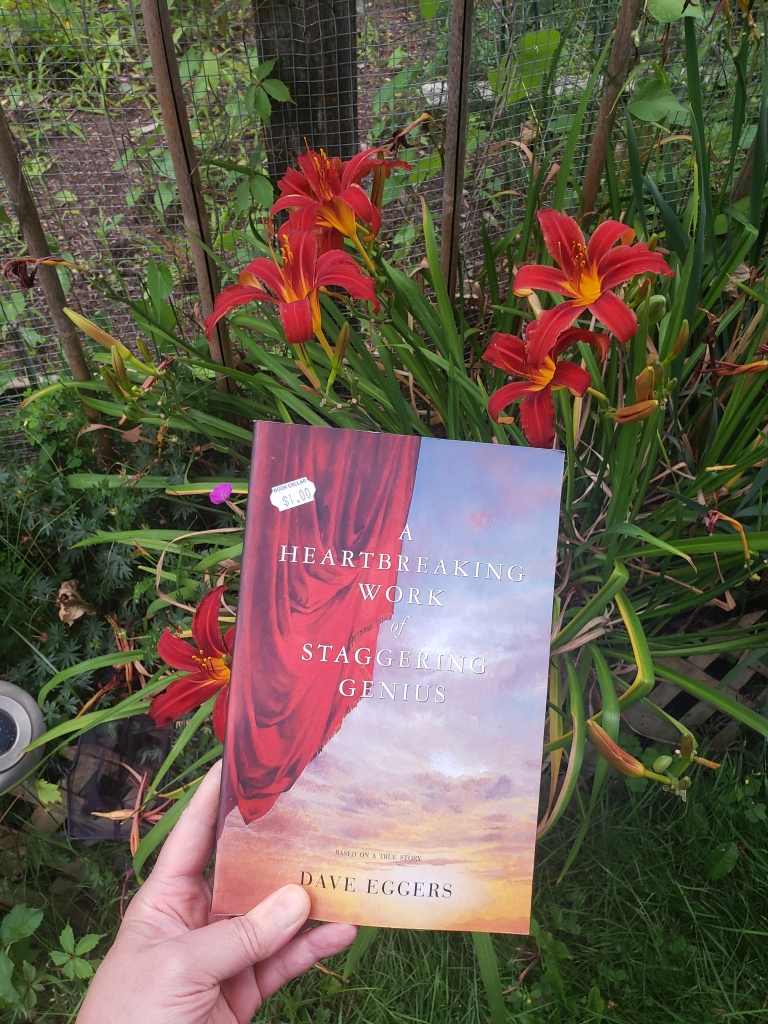Image of A Heartbreaking Work of Staggering Genius by Dave Eggers taken in front of red tiger lilies