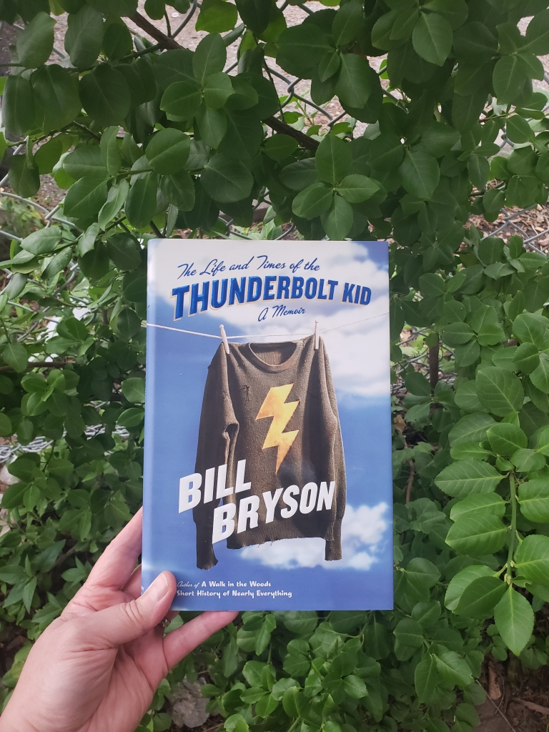 Image of The Life and Times of The Thunderbolt Kid by Bill Bryson taken in front of leafy vegetation