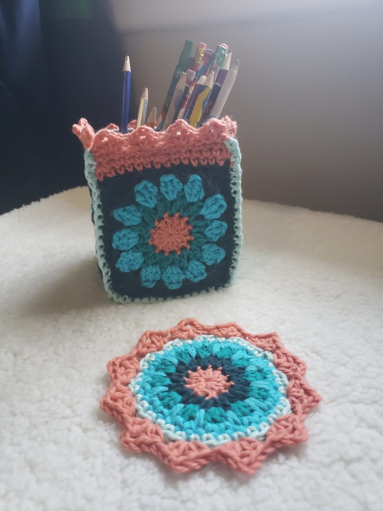 Crochet pencil holder and matching coaster in sea colours of blue and coral, photographed on white sherpa fabric.