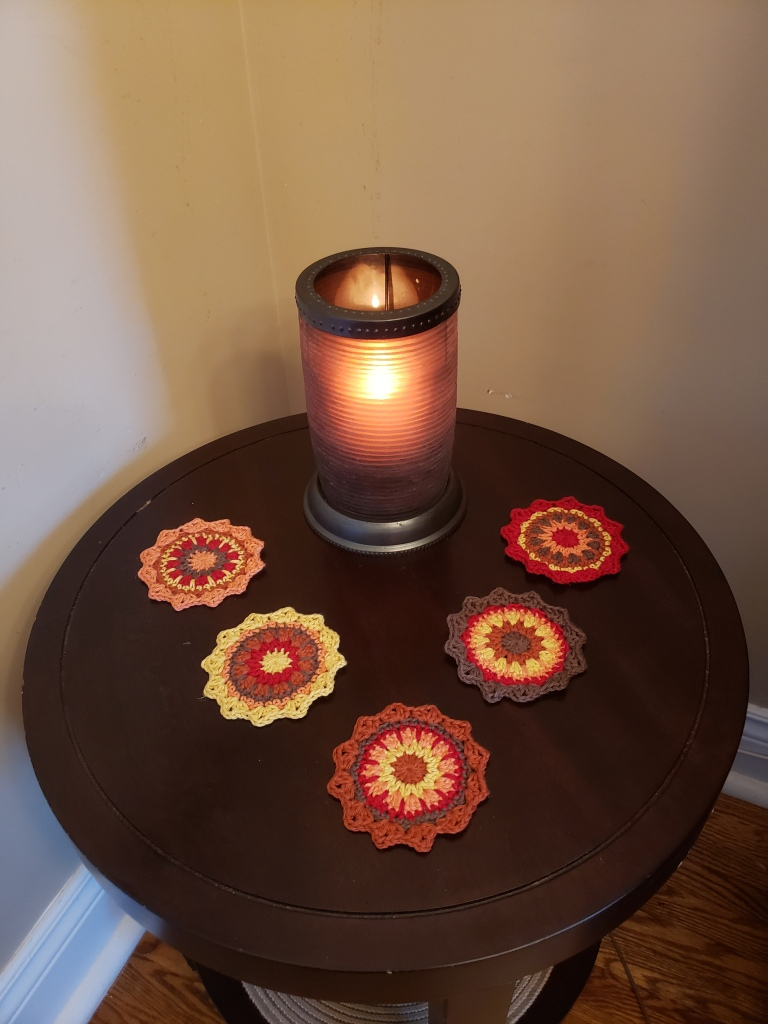5 Crochet Mandala coasters in rust colours, on a dark brown wood table with a brown and yellow flame tinged candle holder burning in the background.