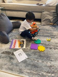 Picture of a little boy reading a book about cranes while assembling a toy crane