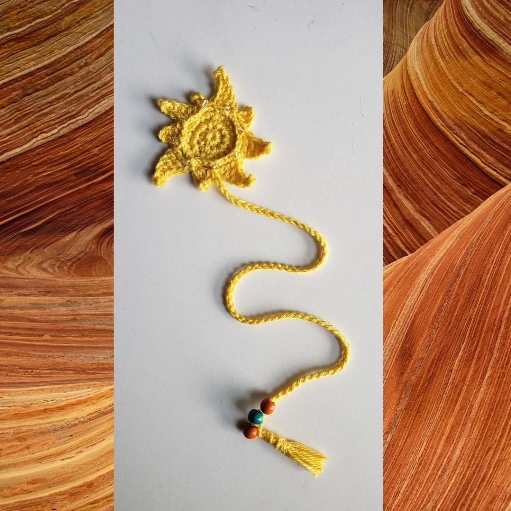Crochet Sunshine beaded bookmark photographed on a white background on top of rust coloured sand dunes as a backdrop