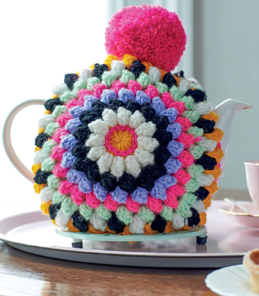 Tea cosy on a white tea pot from the Mindful Crochet Pattern book, in bright colours with a bright pink pom pom on top
